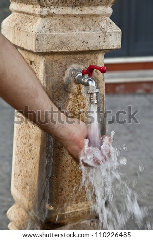 Hand of a man who takes the water that comes out of a fountain - stock photo