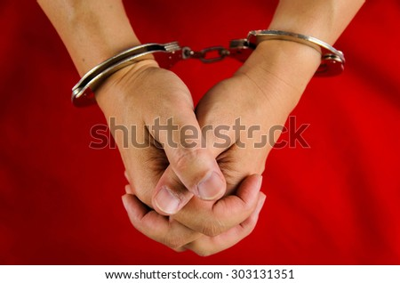 Hand of a man with handcuff on red background - stock photo