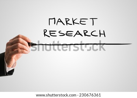 Hand of a man writing Market research on a virtual screen with a marker pen with copyspace below.