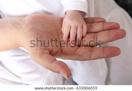 hand of a mother holding his newborn girl hand