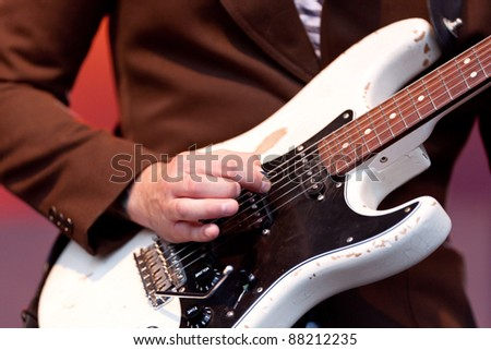 Hand of a musician playing a guitar - stock photo