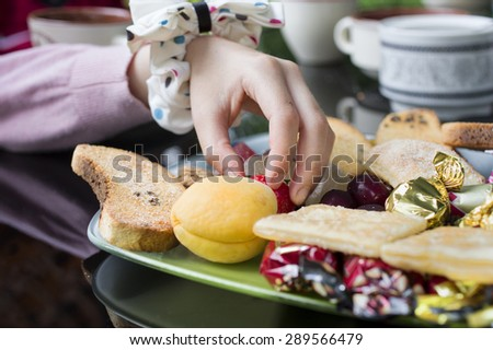 Hand of a naughty little girl picking up candies and fruits from a plate, concept of unhealthy eating, shot with blurred foreground