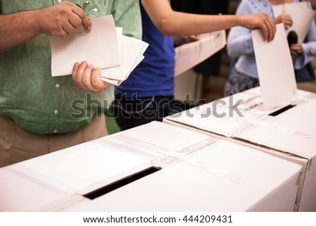 Hand of a person casting a ballot at a polling station during voting. - stock photo