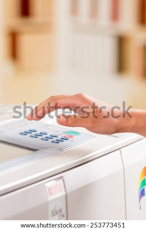 hand of a person using copy machine selective focus - stock photo