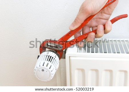hand of a plumber with pliers and radiator - stock photo