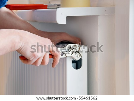 hand of a plumber with wrench and radiator - stock photo
