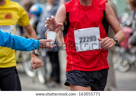 Hand of a volunteer giving a can of water at a refreshment point in a marathon race to an athlete, with the hand of the runner grabbing the water - stock photo