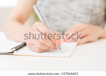 Hand of a woman filling out a notebook