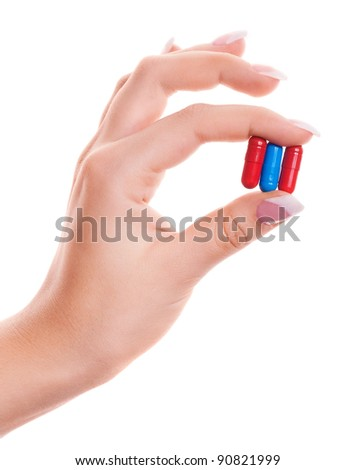 hand of a woman holding three pills, isolated against white background