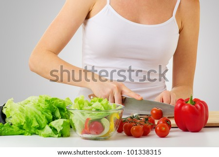 hand of a woman housewife preparing dinner, vegetables: tomatoes, peppers, lettuce on a cutting board in kitchen - stock photo