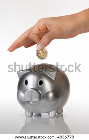 Hand of a woman putting 2 euros in a piggy bank