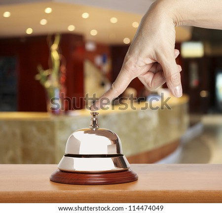 Hand of a woman using a hotel bell - stock photo