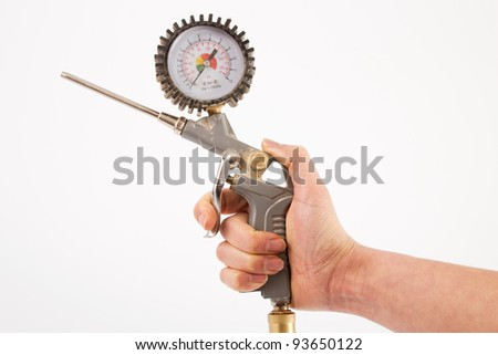 Hand of a woman with a pistol of a compressor in front of a white background - stock photo