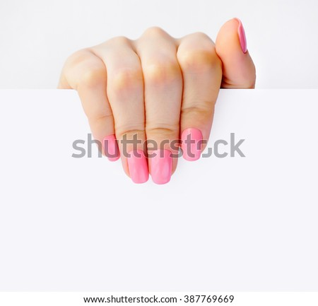 Hand of a woman with pink manicure holding white empty paper - stock photo