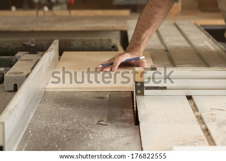 hand of a worker while cutting with circular saw