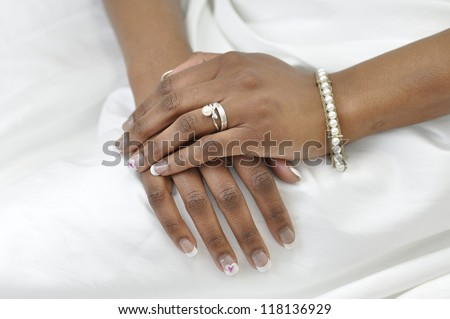 hand of a young african woman wearing a wedding ring and pearl bracelet - stock photo