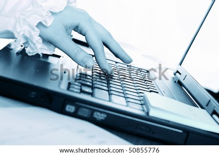 hand of a young business woman working for a laptop. Workplace of business people.