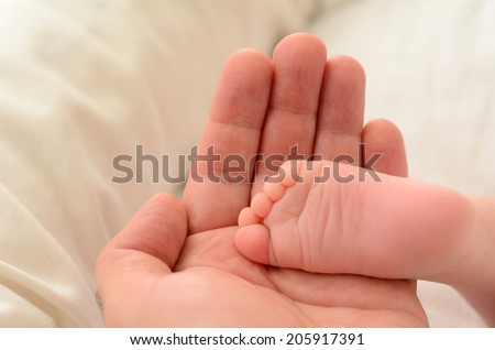 Hand of a young father touch his newborn baby foot (4 week old). copyspace,  Concept photo of newborn, baby, mother, motherhood, parenting and lifestyle - stock photo