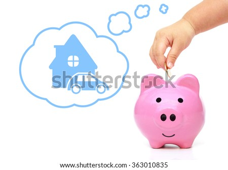 hand of a young female child putting a coin into a pink piggy bank thinking of buying a new house and a car - kid saving money for future concept - stock photo