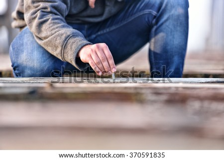 Hand of a young man extinguishing cigarette on a old bridge. Concept quit smoking. Selective focus - stock photo