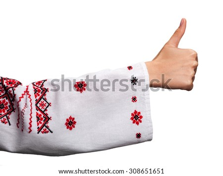 Hand of a young woman in the Ukrainian national clothes shows symbol ok with thumbs up isolated on white. Embroidered shirt.