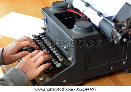 Hand of a young woman writer writing on antique typewriter.Side view - Type Writing Concept - stock photo
