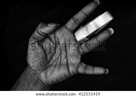 Hand of African-American woman with cast for arthritis or fractured finger - stock photo