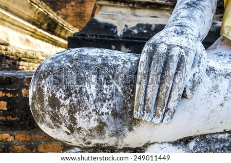 Hand of an ancient Buddha statue - stock photo