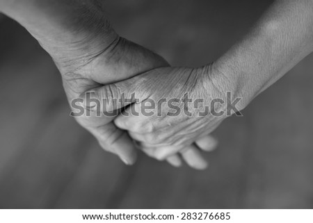 Hand of an elderly woman holding the hand of an elderly man. black and white. - stock photo