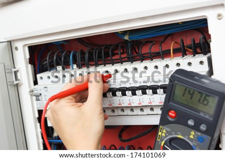 Hand of an electrician with multimeter probe at an electrical switchgear cabinet - stock photo