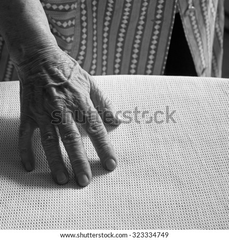 Hand of an ironing old woman