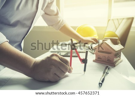 hand of architect drawing on architectural project,Projecting with pencil on the urban drawings. home planning on blueprint ,Architectural plans design home, on the desk, selective focus,vimtage color - stock photo