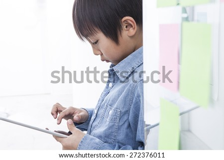 Hand of Asian boy playing Tablet fun - stock photo
