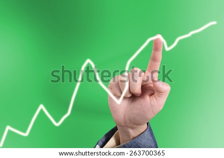 Hand of Asian business man pointing a line graph on a virtual touch screen - stock photo