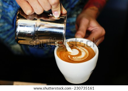 hand of barista making latte or cappuccino coffee pouring milk making latte art  - stock photo