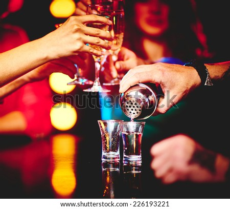 Hand of barman pouring drink into glasses in the bar - stock photo