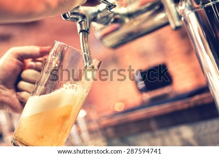 Hand of bartender pouring a large lager beer in tap. Soft, vintage instagram effect on photo - stock photo