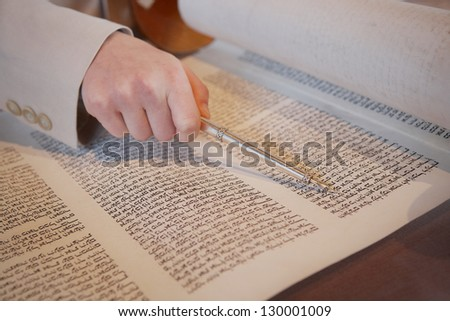 Hand of boy reading the Jewish Torah at Bar Mitzvah - stock photo