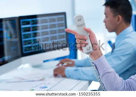 Hand of broker holding telephone receiver - stock photo