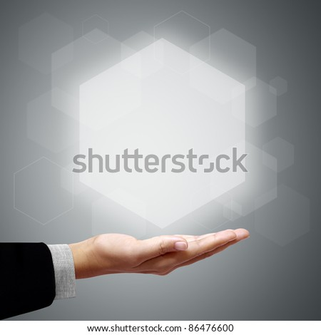 Hand of business man have Hexagon above on gray background - stock photo