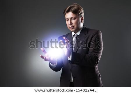 Hand of Business Man Hold light on dark background - stock photo