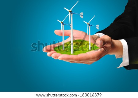 Hand of Business Man hold Turbine Power Generator as renewable energy concept  - stock photo