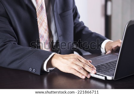 Hand of Business man holding Disk insert to laptop computer  - stock photo