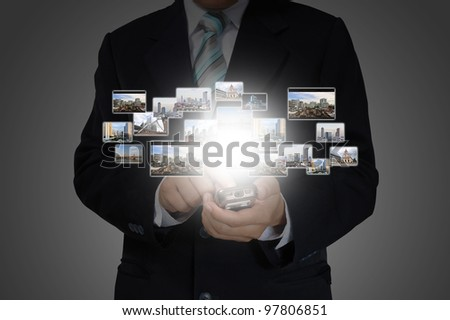 Hand of Business Man Pressing or Pushing touch screen of Mobile Smartphone on Photo sreaming - stock photo
