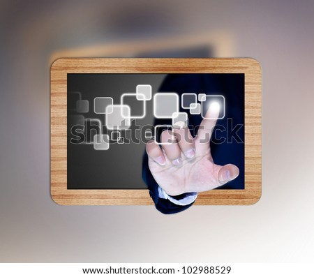 hand of business man pushing a button on a touch screen interface on black board