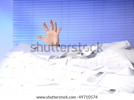 hand of business man sticking out of a desk full of papers - stock photo