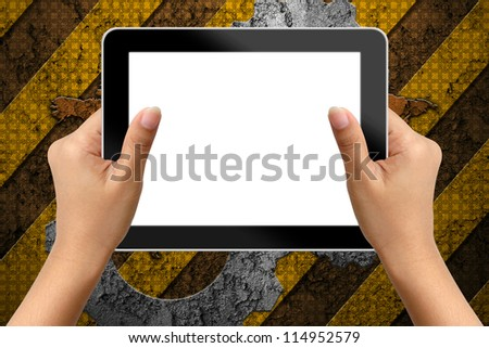 Hand of business woman holding digital tablet with blank screen on industry background - stock photo