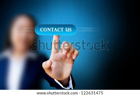 hand of business women pushing a button on a touch screen interface on contact us button - stock photo