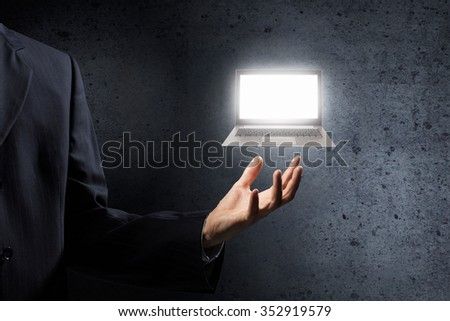 Hand of businessman holding glowing laptop in palm