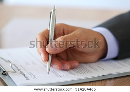 Hand of businessman in suit filling and signing with silver pen partnership agreement form clipped to pad closeup. Business success, contract, paperwork or lawyer concept - stock photo